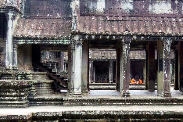 Monks dressed in orange perform ceremony in Angkor Wat Temple