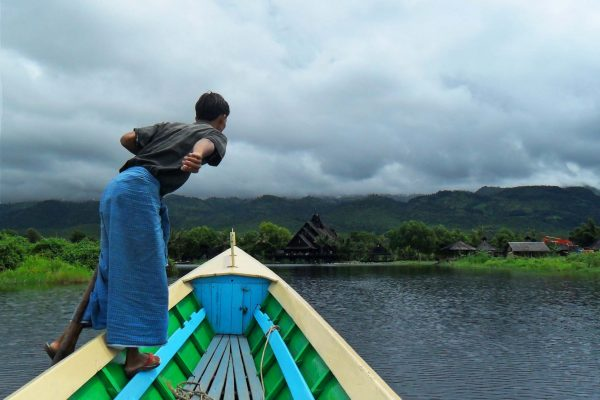A standing boatman rows a bright green and blue boat under gloomy skies on Inle Lake, Myanmar.