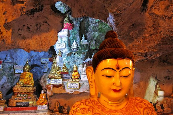 A large image of the Buddha in the foreground, with dozens of smaller images in the cave in the background at the Pindaya Cave, Shan State, Myanmar.