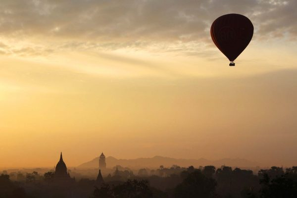 A red hot air balloon floats over the hazy field of temples in Bagan, Myanmar.
