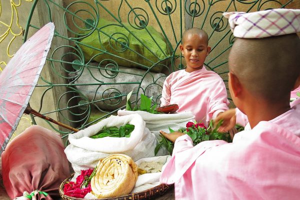 Novice nuns buy flowers at a market in Bagan, Myanmar. The girls wear pink robes and their heads are shaved.