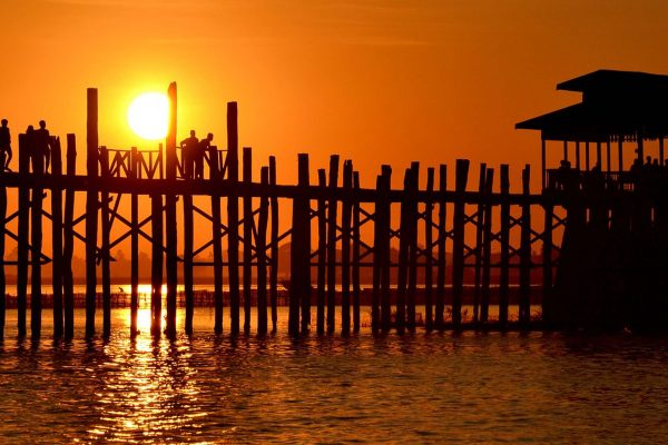 An orange sunset beind U Bein Bridge, the longest teak wood bridge in the world, Mandalay, Myanmar. A few people are standing on the bridge.