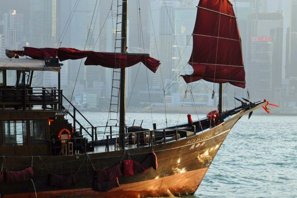 A traditional wooden junk boat with red sails in Hong Kong Harbor