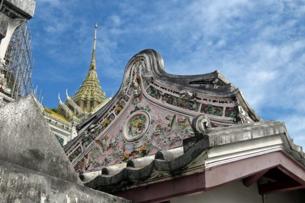 A building decorated with a porcelain mosaic floral design on the grounds of Wat Arun, with the spire of the chedi in the background; Bangkok, Thailand