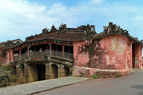 The iconic Japanese covered bridge made of wood, stone, and pink-painted cement spans a canal in Hoi An, Vietnam