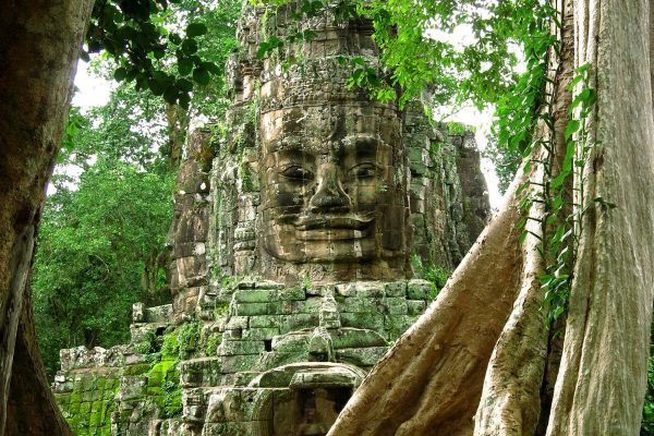 A large stone face adorns a gate to Angkor Thom