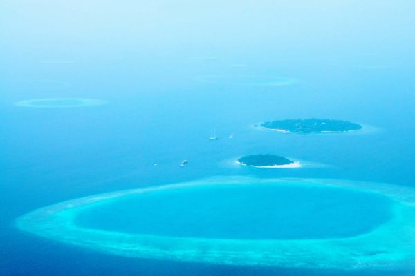 Maldives from above-- aerial view of boats, small round islands, and rings of coral atolls