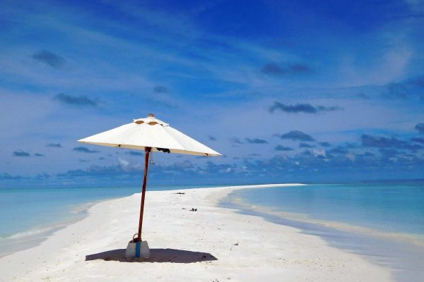 A lone white beach umbrella sits on a sand bar in the Maldives, which blue water laps the shore from either side.