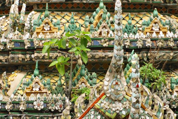 Detail of mosaics tile decoration at Wat Arun, Bangkok, Thailand. Small branches are growing out from the colorful tiles.