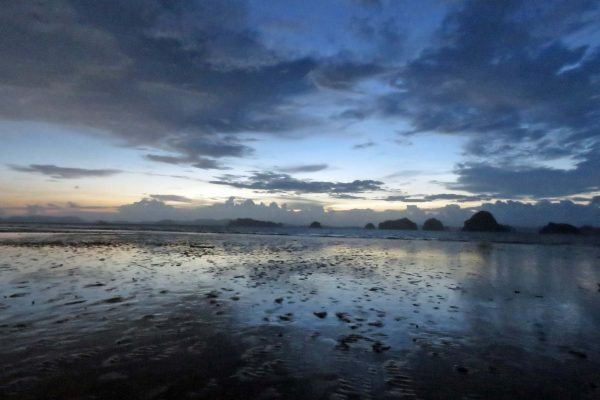 Moody sunset on a beach in Krabi, Thailand; the sky is full of blue and gray clouds, reflected in the water washing up on the sand.