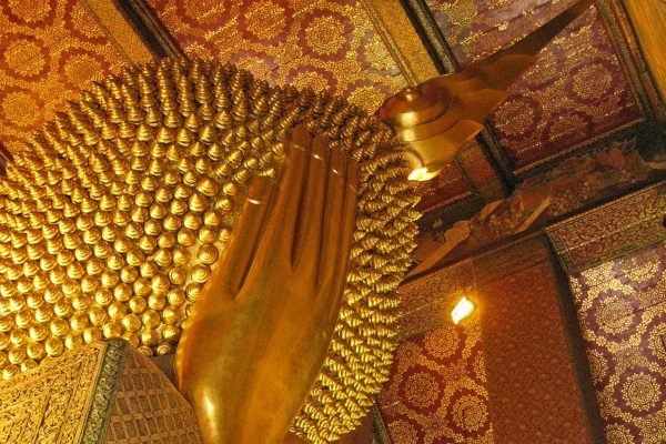 An enormous golden statue of a Reclining Buddha, showing just the back of his head with golden coils of hair and his hand propping up his head; the ceiling is decorated in red and gold designs, at Wat Pho, Bangkok, Thailand.