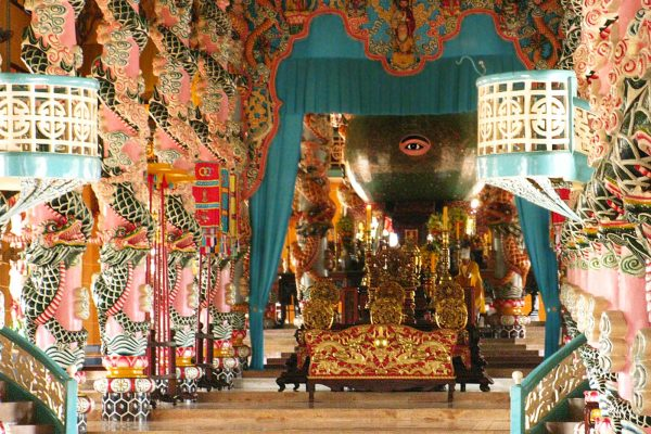 The truly unusual, unique and somewhat surreal Cao Dai Temple with pink and green pillars decorated with dragons and a large globe with a painting of a single human eye looking out at the central hall, in Tay Ninh, Vietnam.
