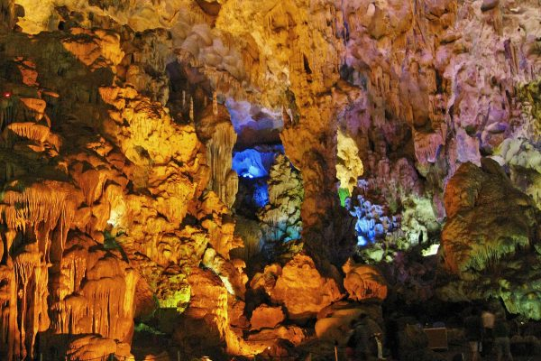 "Inside the ""Surprise Cave,"" lit by multi color lights casting shadows on the stalactites in Halong Bay, Vietnam"