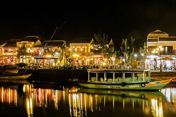 A green tourist boat sits empty in the water while a row of brightly lit shops sit in the background at night in Hoi An, Vietnam