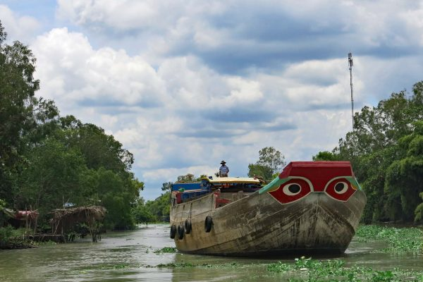 The watchful eyes painted on the front of a rice barge looking out for water dragons on the Mekong Delta, Vietnam. A man wearing a hat stands on the boat.