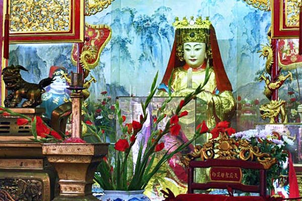 A shrine dedicated to the Goddess of the Sea, in Ho Chi Minh City, Vietnam. An image of her wearing a golden headdress is surrounded by flowers and other religious symbols.