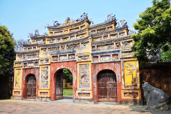 Entrance to the Imperial Citadel with three arches, painted in faded yellow and orange, Hue, Vietnam