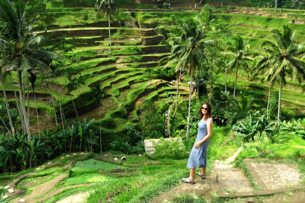 Ilex founder Holly Monahan smiling in a long blue dress while standing on a step overlooking the Tegallalang Rice Terraces in Bali, Indonesia