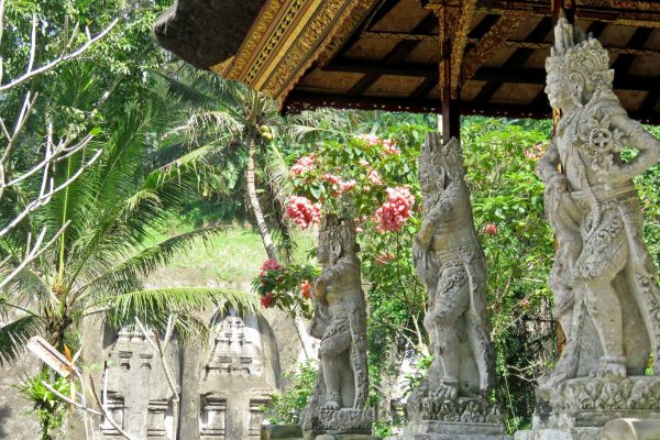 Three carved figures beneath a canopy at Gunung Kawi Temple in Bali, Indonesia