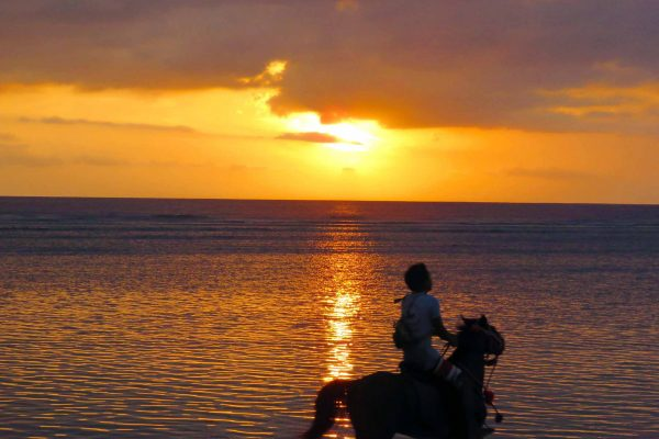 A man goes horseback riding on the beach as the sun sets on Gili Trawangan, Indonesia