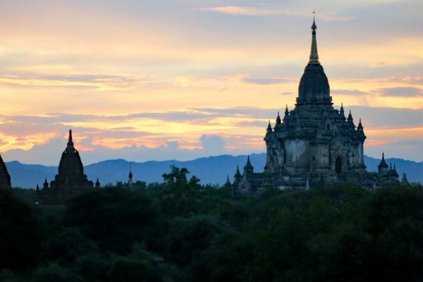 The soft glow of sunset over the plain of temples in Bagan, Myanmar. A large temple with a central spire sits to the right.