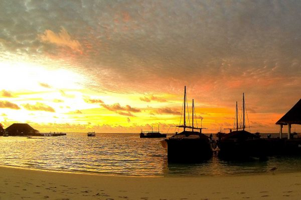 A fiery sunset in the Maldives--the sky glow in orange while boats sit at the jetty