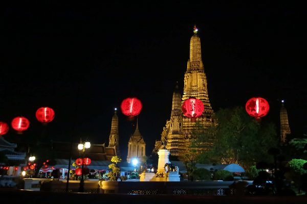 Wat Arun Temple lit up at night and glowing with a golden hue, behind a string of round red lanterns, Bangkok, Thailand