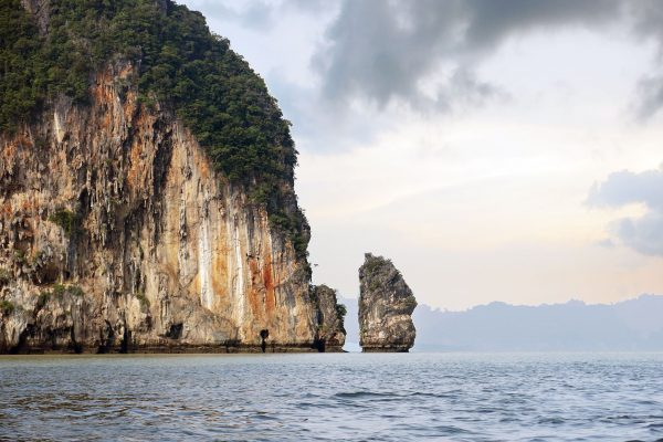 A large craggy cliff face with green trees growing on top juts out of the sea, a much smaller cliff sits upright like a stone tower beside it. Phang Nga Bay, Thailand
