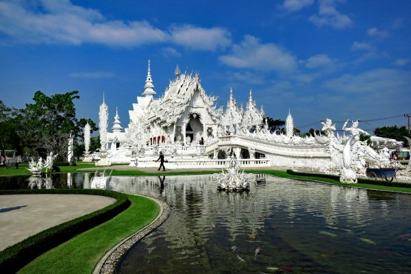 An ornate, completely white Thai-style temple sits behind a pond with fountains, the White Temple, Wat Rong Khun, Chiang Rai Province, Thailand.