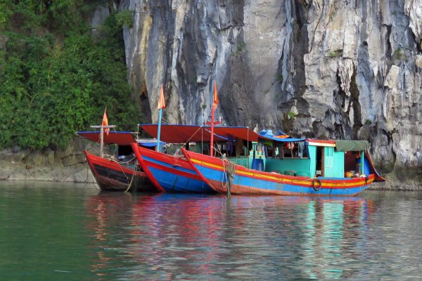 Three cute and colorful boats painted blue, red, and yellow lined up in Halong Bay, Vietnam.