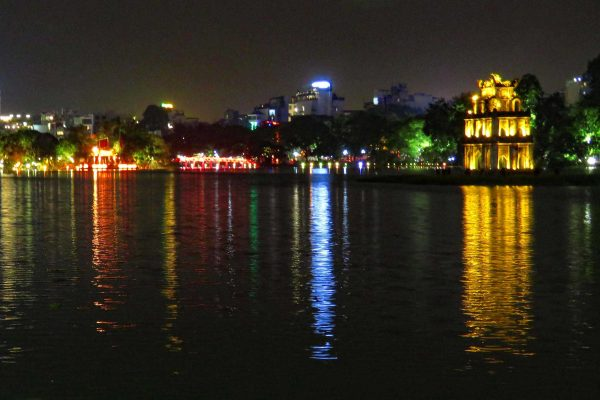 Glowing jewel tones in red, yellow, and blue light up the night and cast long reflections on Hoan Kiem Lake, Hanoi, Vietnam