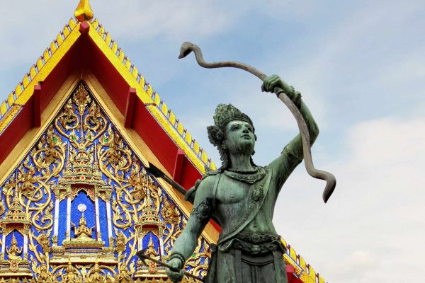 Statue of Lord Rama (in green-tinged bronze) holding his bow aloft in front of The Bhuddhaisawan (Phutthaisawan) Chapel (with gold decoration on a lapis blue background) at the National Museum Bangkok, Thailand.