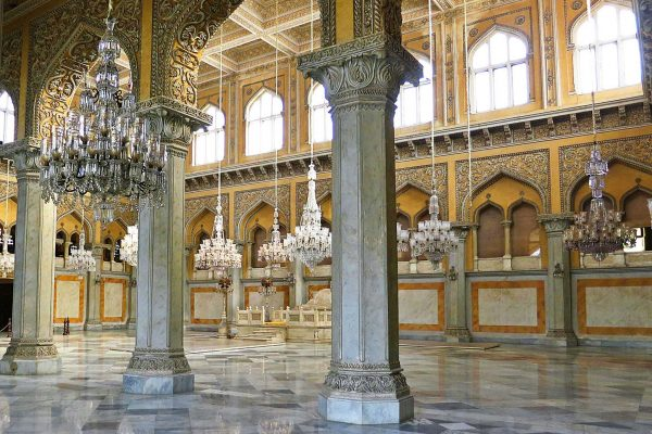 A ballroom with massive chandeliers and carved columns in the Chowmahalla Palace, India.