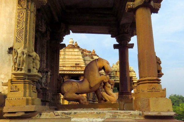 A statue outside of a temple in Khajuraho, India., showing a lion and woman embracing.