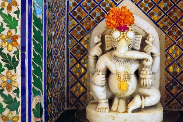A small marble statue of the elephant-headed god Ganesh at Udaipur's City Palace. A fresh marigold adorns his head.