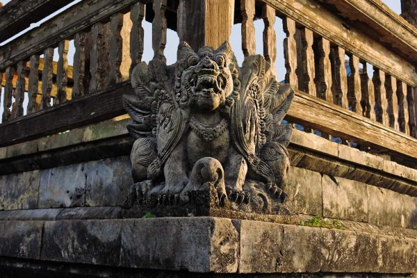 A stone carving of the mythical garuda with wings and a lion's body faces out from a corner of the Uluwatu Temple, Bali, Indonesia.