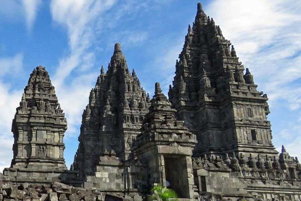 A glorious morning at the Prambanan Temple, Java, Indonesia. The tiered stone spires of three temples and an entrance gate reach up towards a blue sky with puffy clouds.