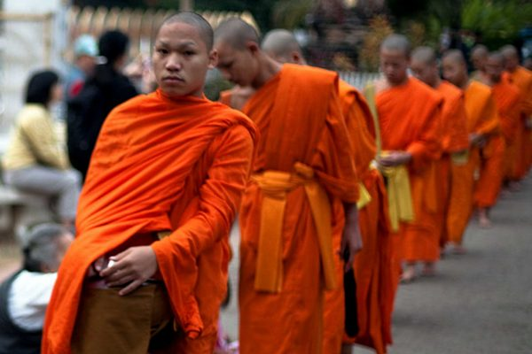 Monks in orange robes line up for alms in Luang Prabang, Laos