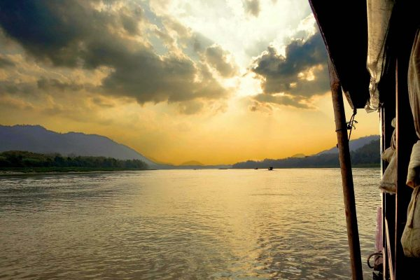 The sun bursts through clouds on the Mekong River, northern Laos, as seen from a boat cruise on the river.