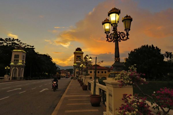 Sunset on the Sultan Iskandar Bridge, Ipoh, Malaysia, with Victorian street lamps and pink and white flowers in the foreground.