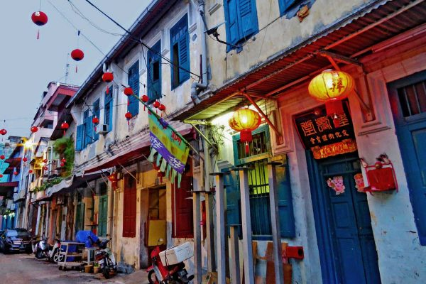 A colorful street with brightly painted doors and red lanterns in Chinatown, Kuala Lumpur, Malaysia