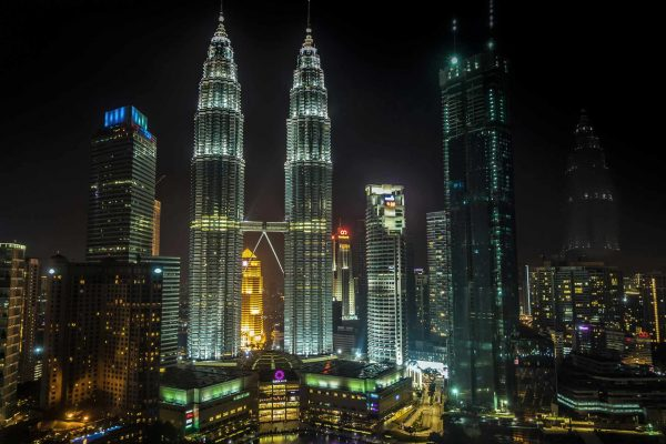 The Petronas-Towers dominate the evening skyline in Kuala-Lumpur, Malaysia. These are the tallest twin towers in the world, linked by a bridge part way up.