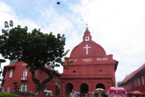 The Anglican Christ Church in Melaka (Malacca), Malaysia stands out for its soft red color and large white cross beneath the church bell.