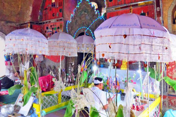 A priest reads scripture at a Buddhist temple in Heho, Myanmar. The priest wears white and is seated under a pink parasol in the highly decorated church.