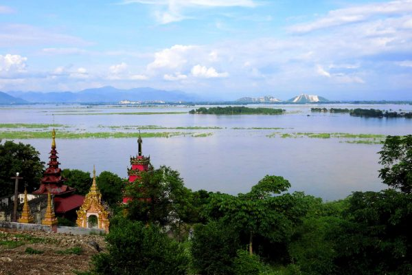 The view from a hillside in Mandalay, Myanmar. Red and gold shrines sit on the hill at the edge of the lake.; mountains are in the distance.