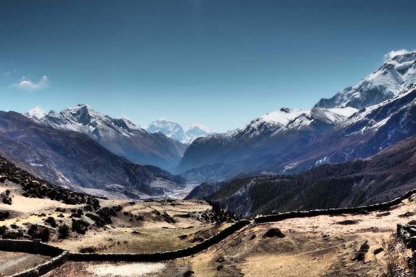 A valley in the Annapurna Mountain Range, Nepal; snow-capped mountains line each side of the valley