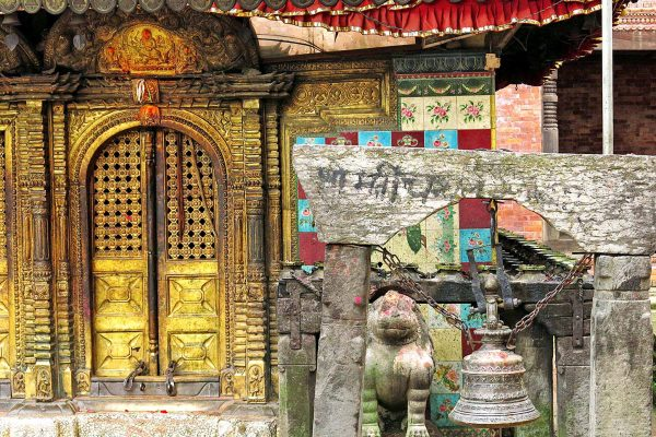 A busy doorway in Kathmandu, Nepal; the temple doors are gold, a bell hangs outside in front of a weathered statue of a lion