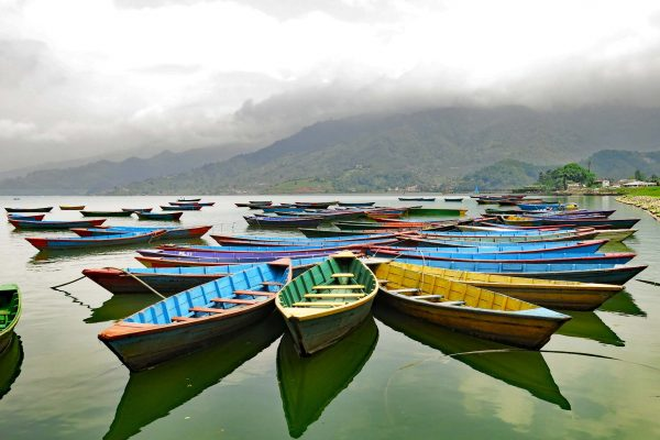 Dozens of brightly painted canoes waiting for passengers on Phewa Tal Lake, Pokhara, Nepal