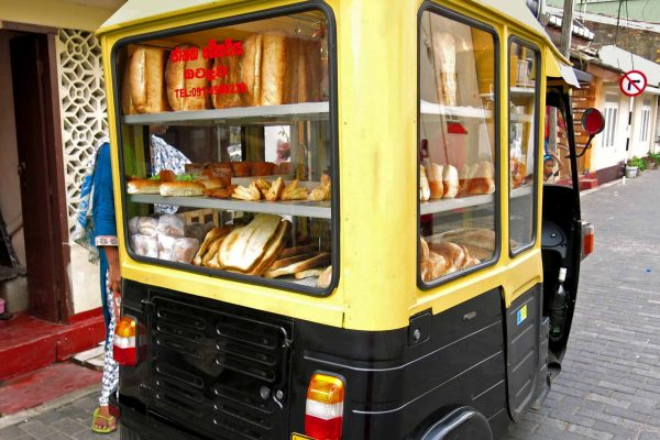 A mobile bakery set up in a auto rickshaw lined with shelves of bread and pastries in Galle, Sri Lanka