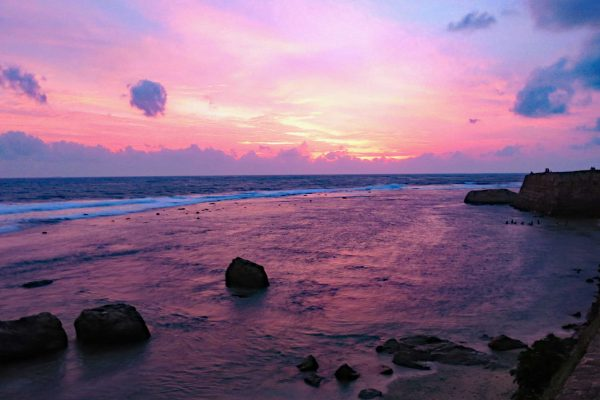 A glorious pink sunset at Galle Fort, Sri Lanka. The pink sky is reflected on the water along the shore.